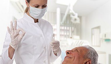Smiling senior man talking to dentist