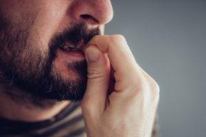 Man biting the tip of his fingernail