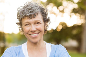 Smiling senior woman with natural looking dental implants
